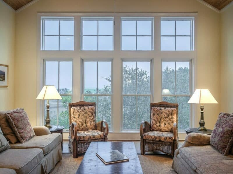 large window in living room, with two sitting chairs and two couches
