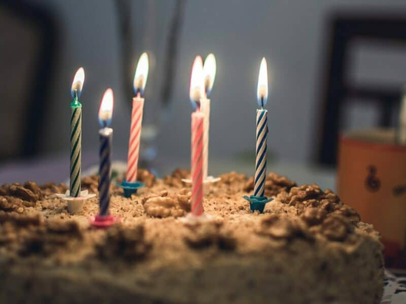 A birthday cake with six colorful glowing candles.