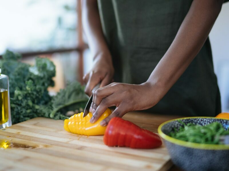 A woman chopping vegetables on a wooden chopping board inside of her home.