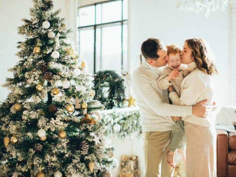 family in front of christmas tree with window in the background