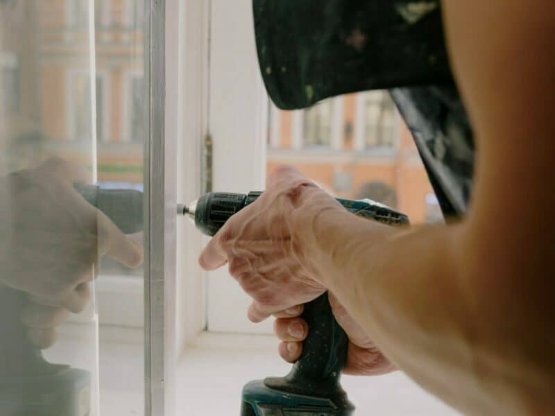 Hands holding a drill that's creating an incision on a wall inside of a home.
