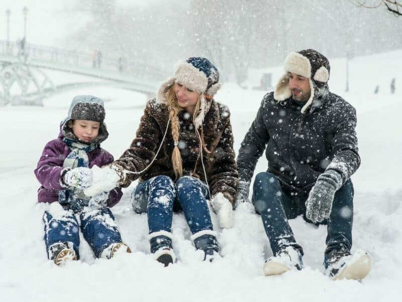 family of three sitting in the snow together