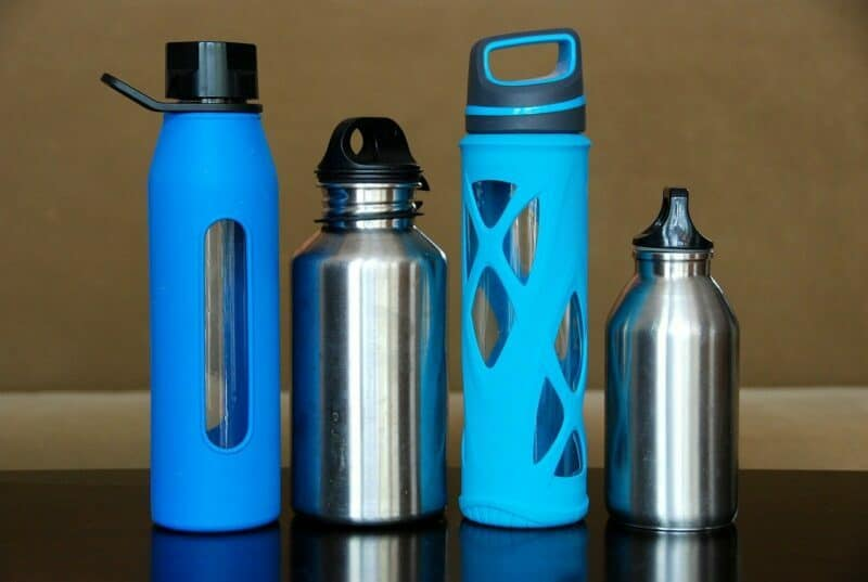 A row of four filtered water bottles made of different materials sit on a dark surface.