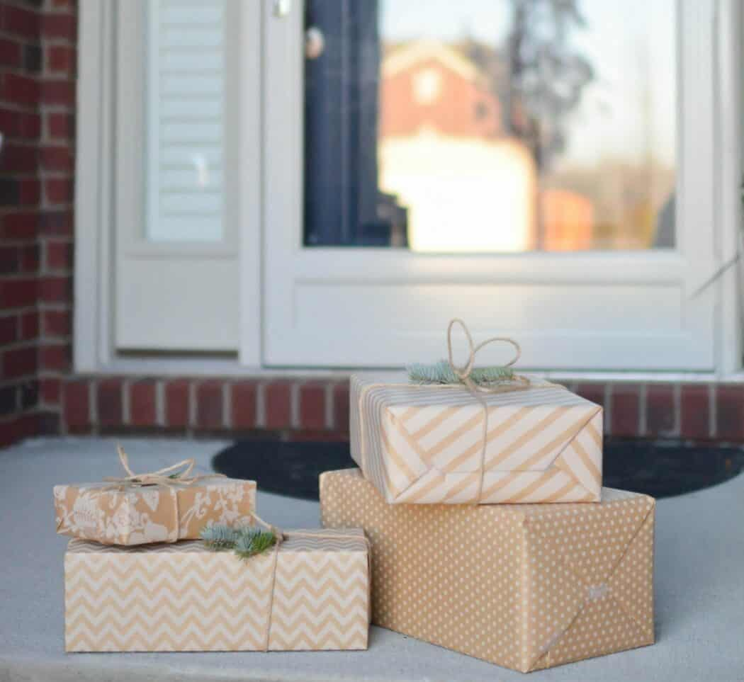 Four packages wrapped in light brown paper are sitting by the front door of a home.