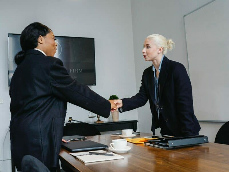 A woman shakes the hand of a female insurance provider inside of an office setting.