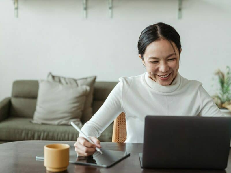 A woman smiles while looking at help laptop and writing on her tablet.
