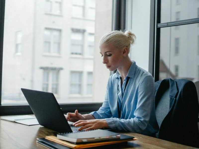 blonde woman in her office at work, on her laptop