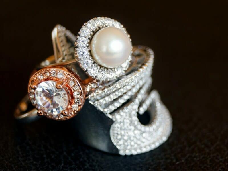 closeup of three rings, one with pearl, others with diamonds