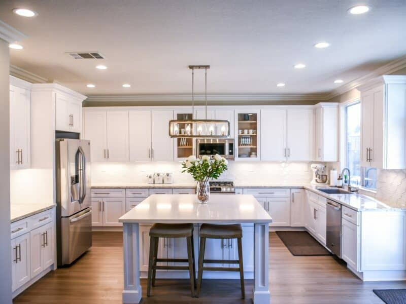 all white kitchen with modern appliances and bright lights