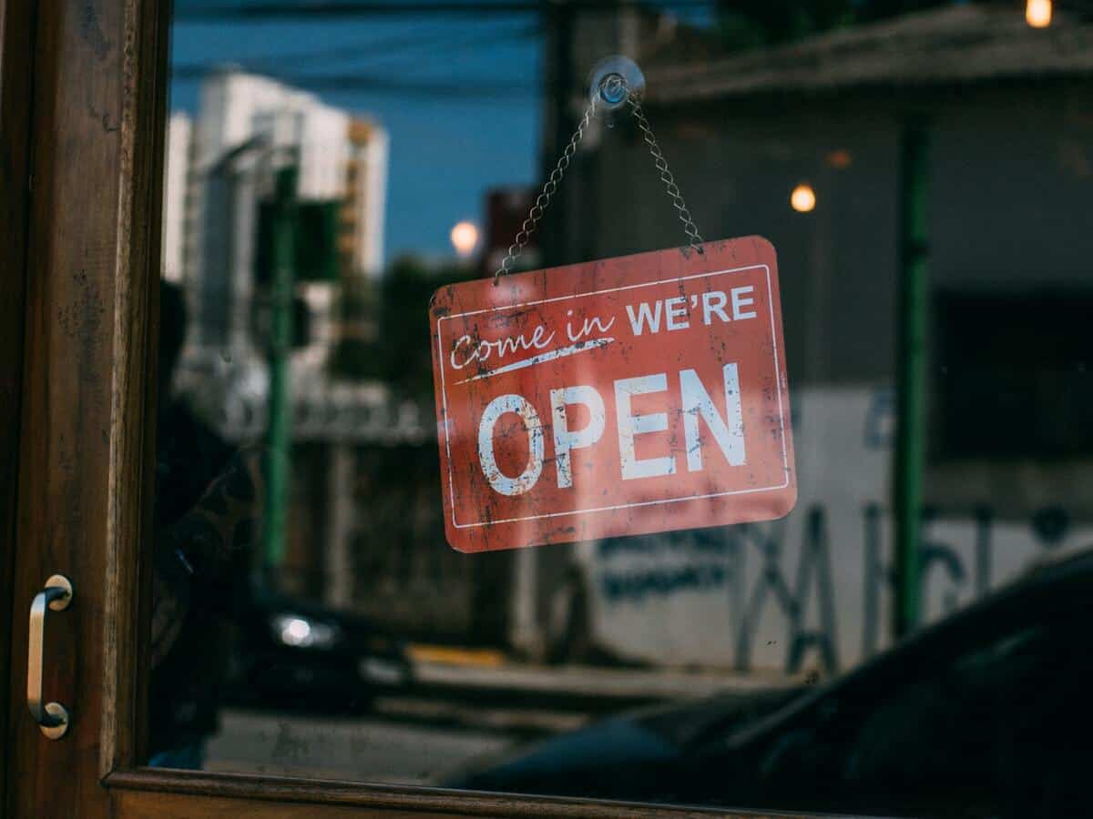 """A red sign reading """"Come in, we're open"""" is on the glass door of a business."""