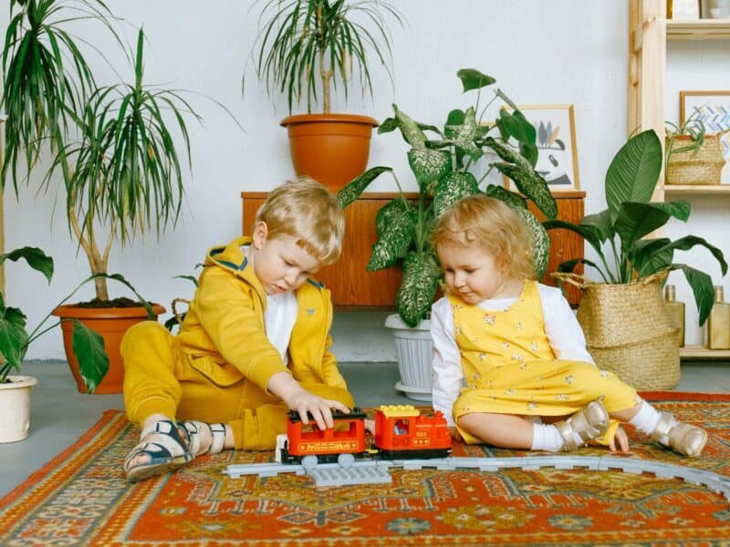 two children playing with a train in front of home plants
