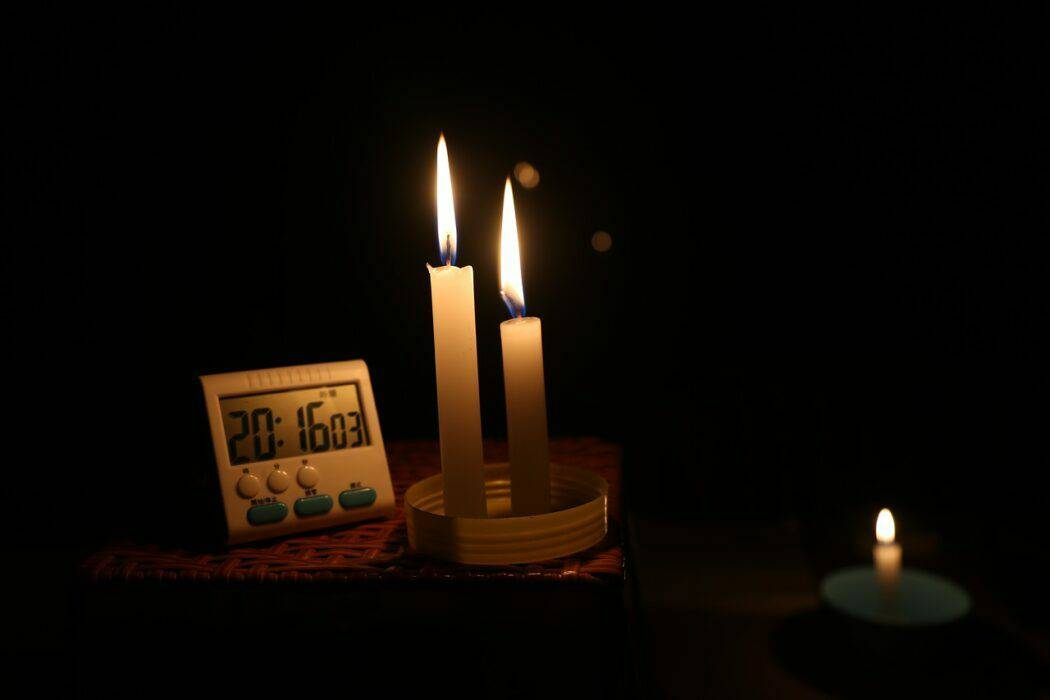 Two lit candles sit on a corner table beside a clock in a dark home.