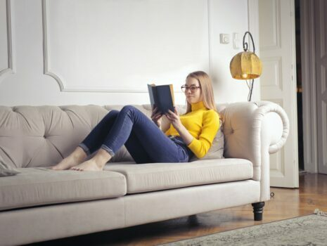 A young woman reading a book on a couch inside of a home.
