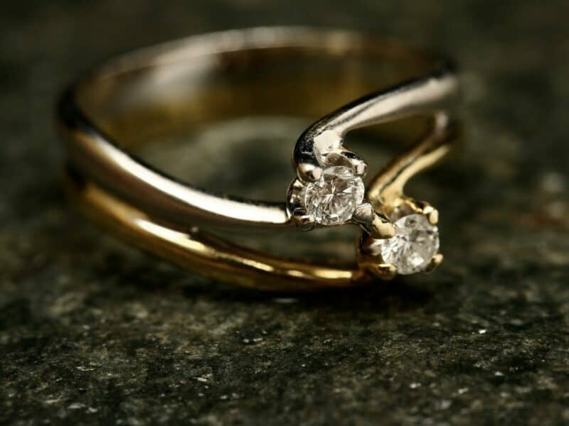 A gold ring with diamonds on top of a dark green counter.