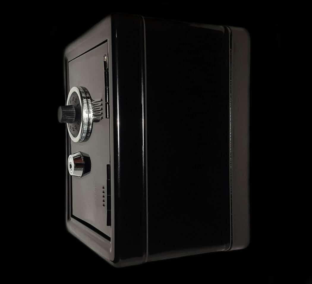 A black home safe box sitting against a black background.
