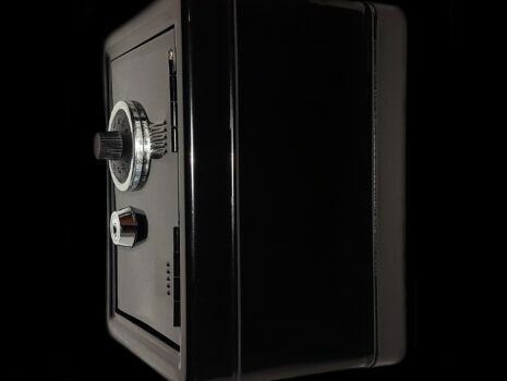 A black home safe box sitting against a black background.