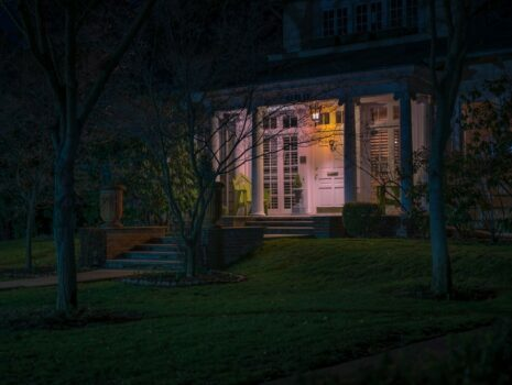 The front of a home surrounded by trees with a security light glowing by the front door.