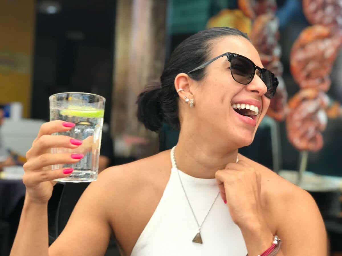 A woman with dark hair is laughing while holding up a glass of water.