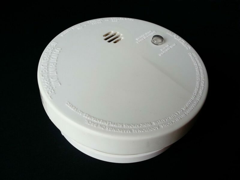 A white smoke detector sitting against a black background.