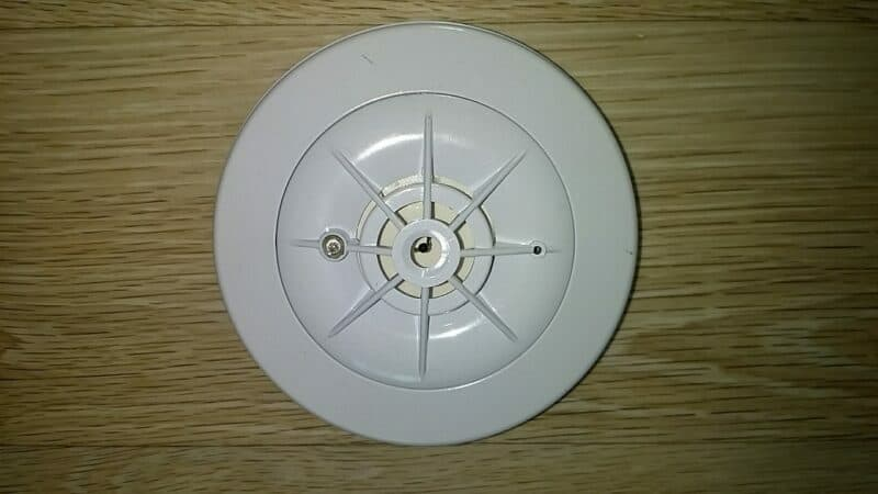 A white smoke detector sitting on top of a brown wooden surface.