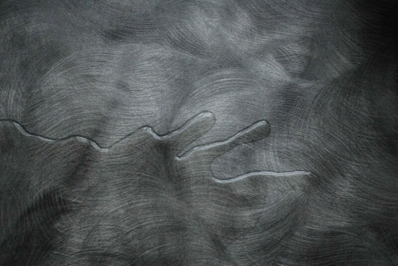 A puddle of spilled water on a gray surface.
