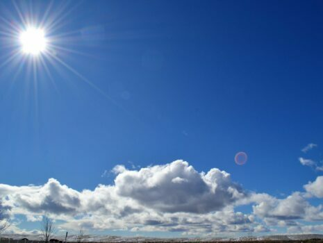 the sun in the corner with clouds and blue sky