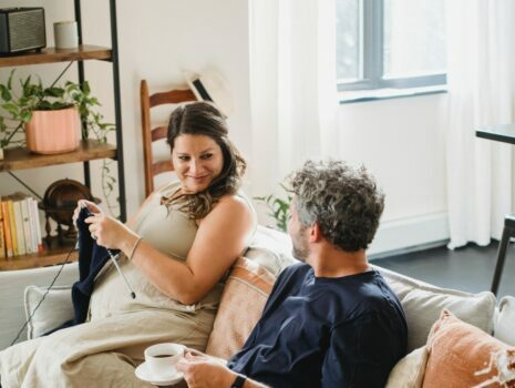 A pregnant woman sits on the couch inside of a living room while knitting next to her husband, who is drinking coffee.