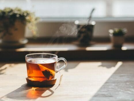 A glass tea cup sitting on a wooden table with a tea bag inside making hot brown tea.
