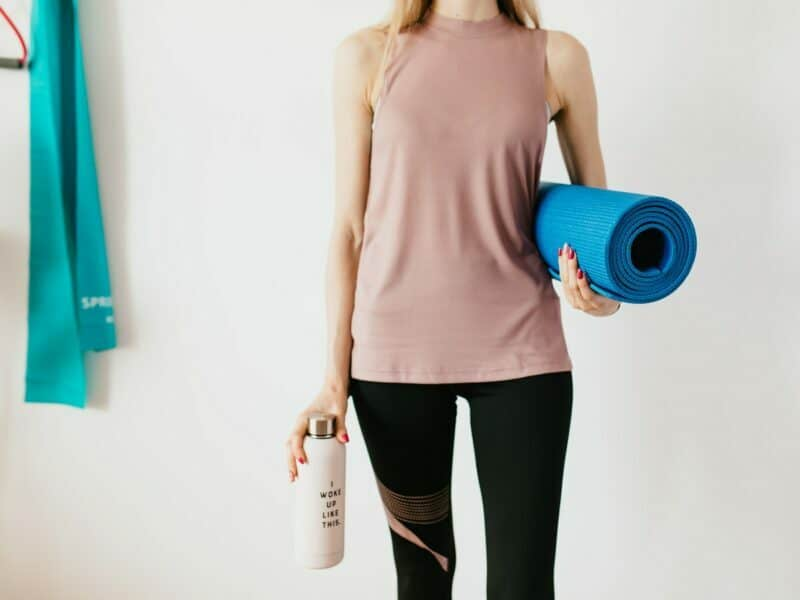"""A woman in work out apparel is carrying a bright blue yoga mat, and an insulated water bottle reading """"I woke up like this""""."""