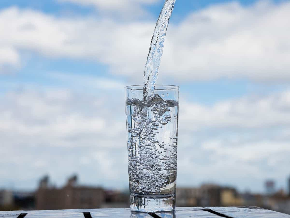 water poured into a clear glass with blue sky in the background