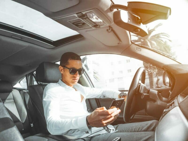 man holding cell phone while driving in car