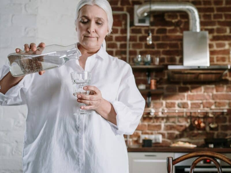 older woman pouring tap water into clear glass for consumption