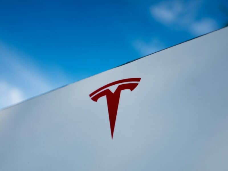 the red tesla logo on a white building