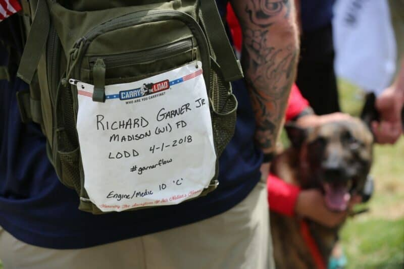 A dark green backpack with a paper attached reading the name of a fallen soldier.