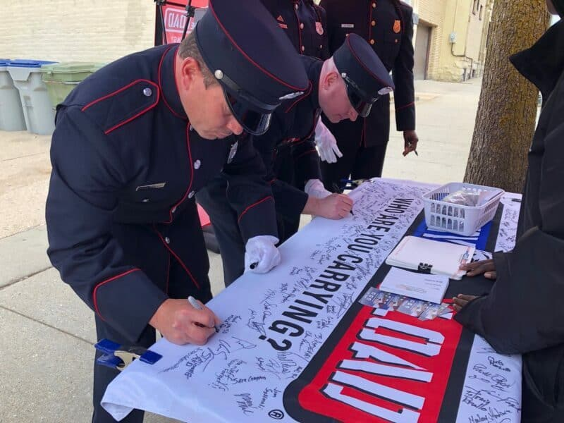 A service member signs his name on a banner on a table at a Carry The Load event.