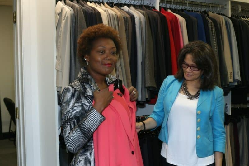 Attitudes and Attire director helps client in boutique.