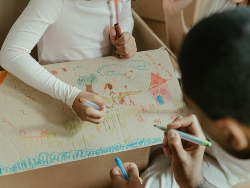 A young girl and her father are coloring on a used moving box.