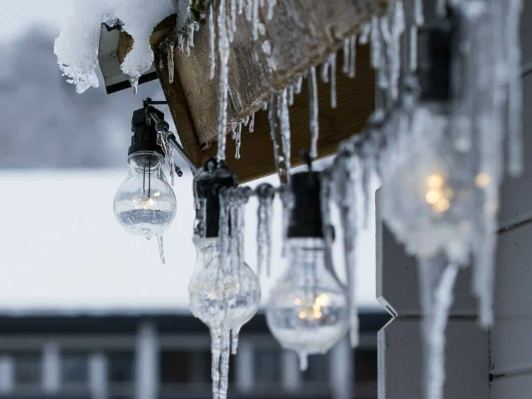 Icicles formed on the eave of a home with lights hanging beneath.