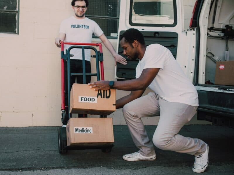 Two young men unload cardboard boxes from a white van onto a metal dolly.
