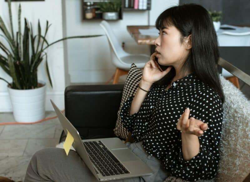 A young woman is speaking on her smartphone while sitting in her living room with a laptop on her legs.