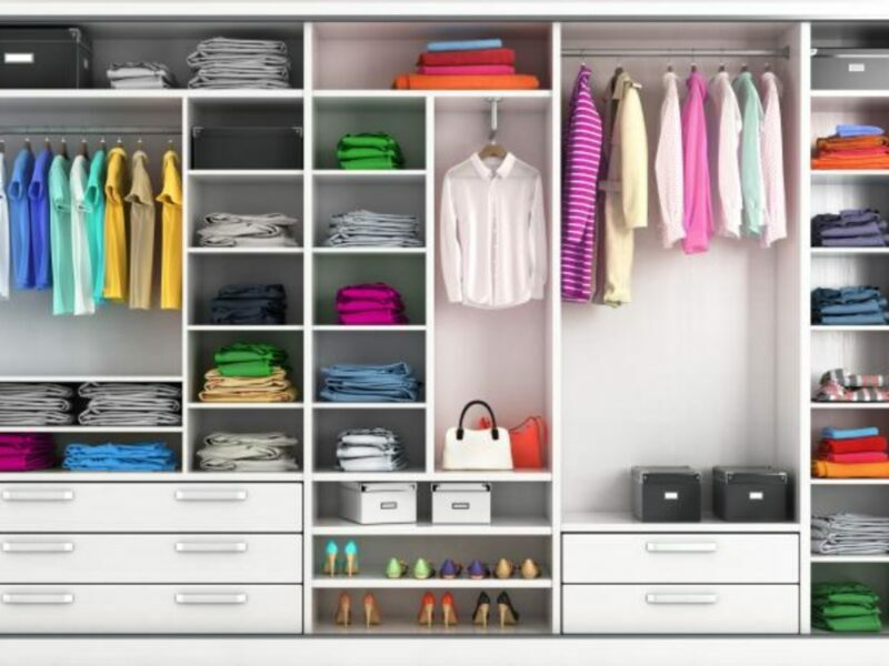 a closet organized by color using bins and hanging clothing