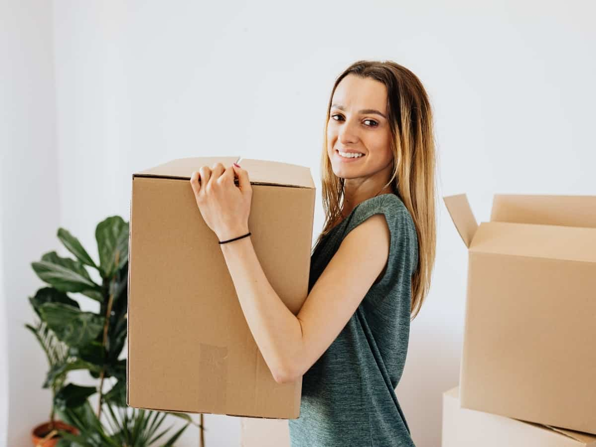 a woman holding a box for a new home
