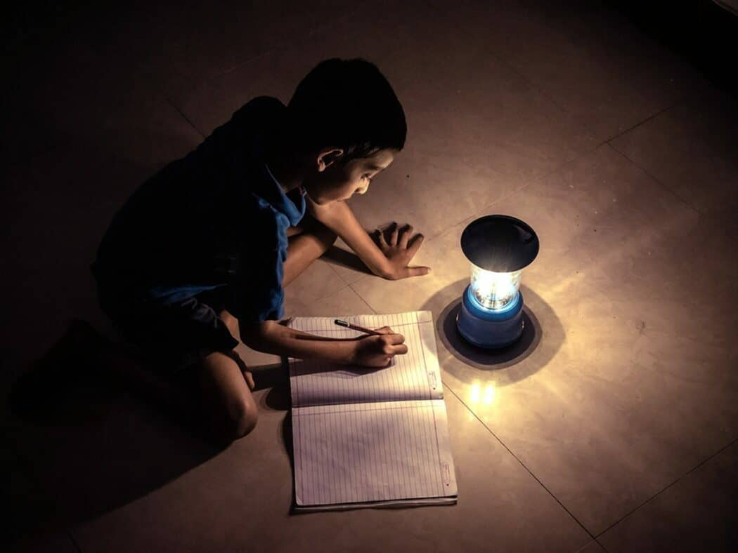 young child reading close to lamp during a rolling blackout