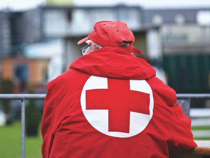 a person wearing red cross jacket