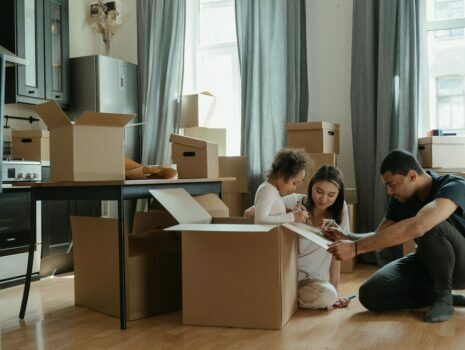 A young girl sits in a moving box as she and her parents decorate the exterior of the box while inside of their living room that's surrounded by other moving boxes.