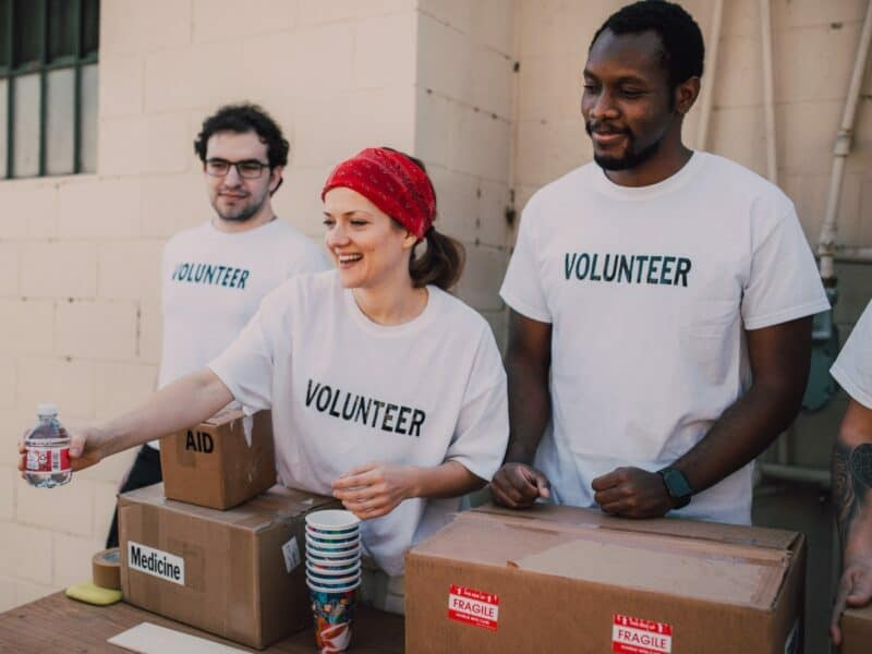 three people volunteering to pass out donated food