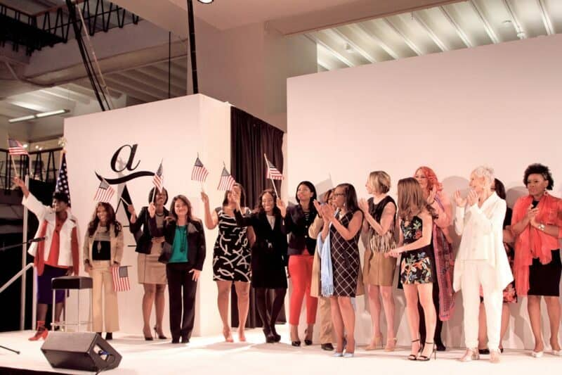 Attitudes and Attire clients and directors standing on stage, waving American flags.