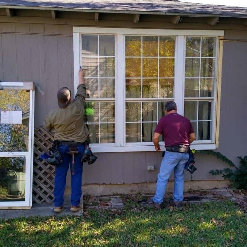 Contractors are working outside of a home on a window replacement for Rebuilding Together North Texas.