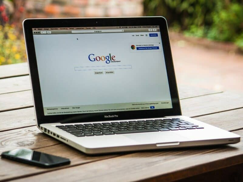a laptop with google on the homepage and a cell phone on the table