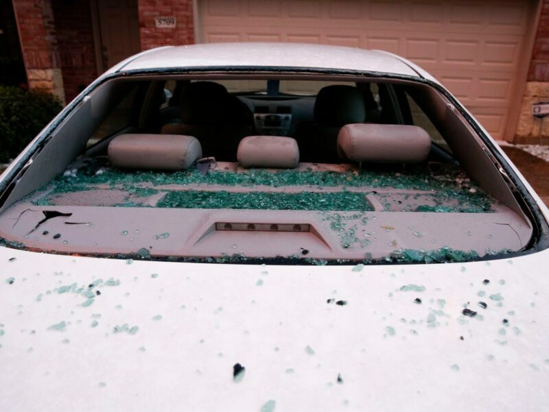 hail damage that results in shattered windshield on white car